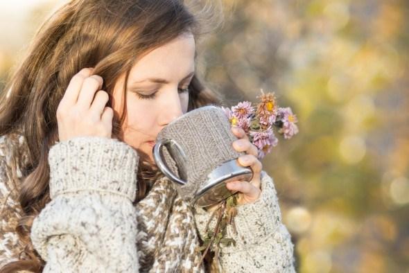 Девушка пьет чай и трав осенью