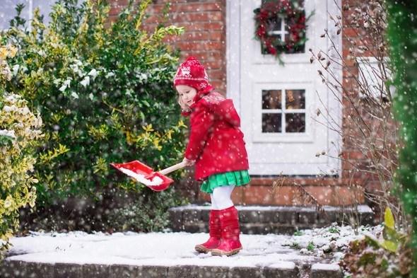 Девочка чистит снег у дома