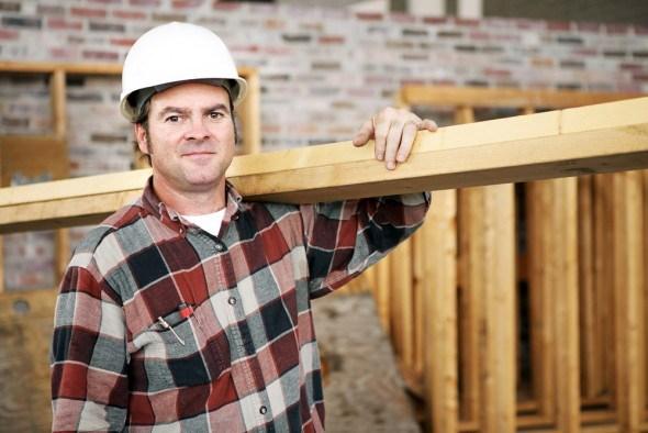 Мужчина-строитель с деревянной балкой